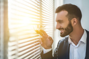 man enjoying sunshine in window 300x200 - Health Benefits of Regular Commercial Window Cleaning at the Office
